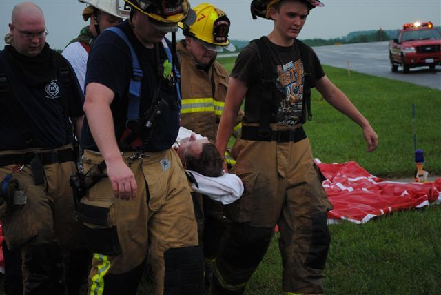 4 Volunteer Fire Fighters help carry a victim on a stretcher