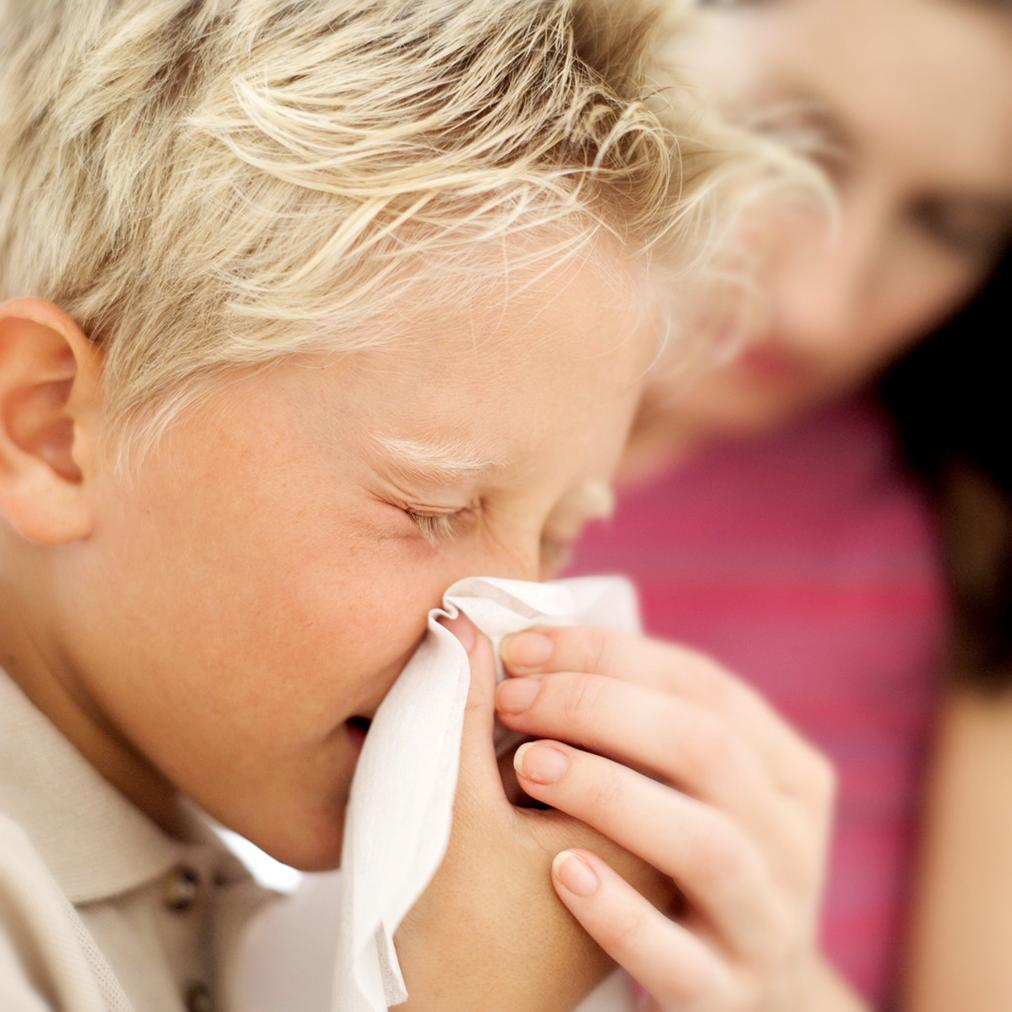 Child sneezing with the flu