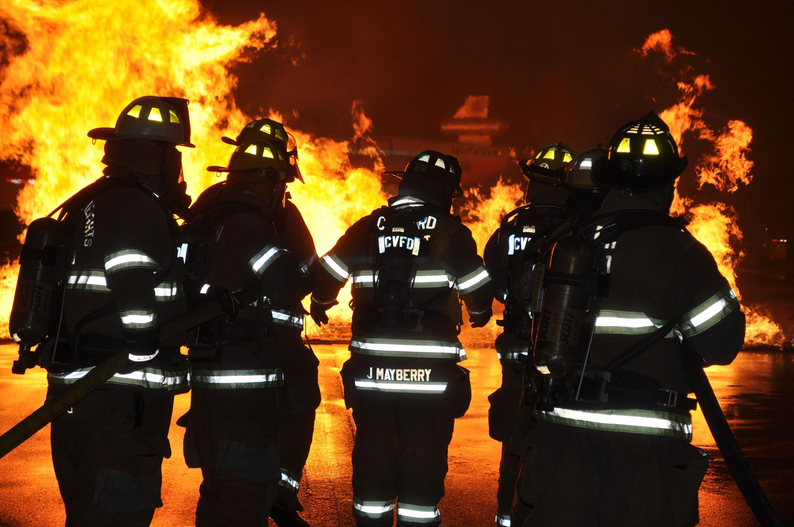 The silhouette of fire fighters at night with the glow of a fire behind them